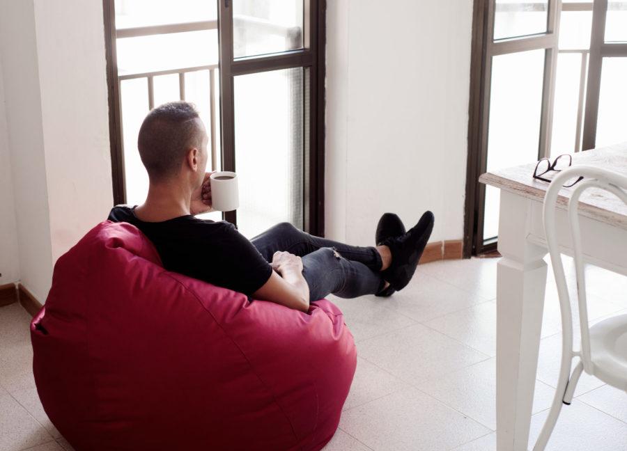 man having a coffee sitting in a bean bag chair